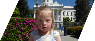 A young white blonde girl with Down syndrome stands in front of the California State Capitol wearing a blue and yellow plaid dress
