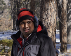 A South Asian young man standing in a snowy forest wearing a big coat, earmuffs, and a red beanie.