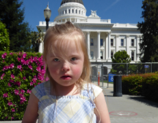 A young blonde white girl with Down syndrome stands in front of the California State Capitol wearing a blue and yellow plaid dress