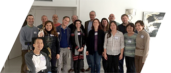The DVU board and staff pose on a staircase, smiling and wearing nametags